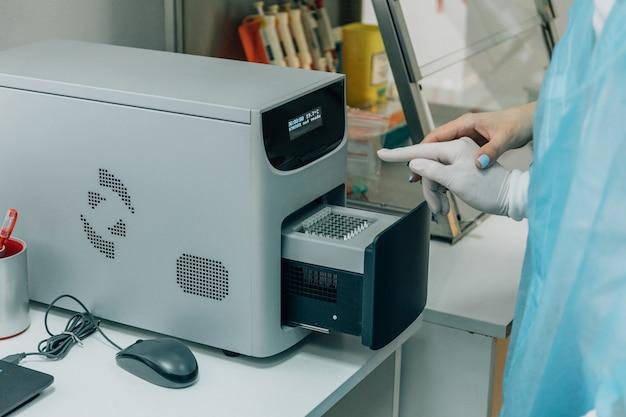 Joven científico, trabajador médico, técnico o estudiante de posgrado trabaja en un laboratorio biológico moderno