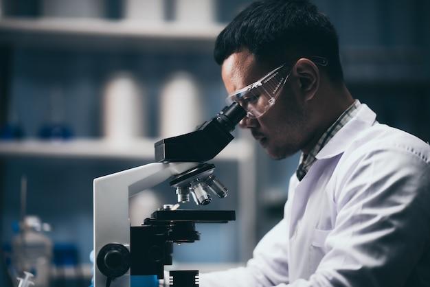 Joven científico trabajando con un microscopio en un laboratorio. joven científico investigando.