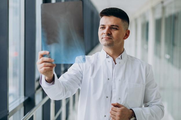 Joven cirujano guapo mirando la radiografía