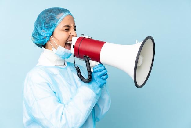 Joven cirujano en uniforme azul gritando a través de un megáfono