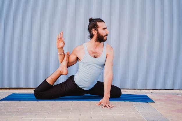 Joven en la ciudad practicando deporte de yoga
