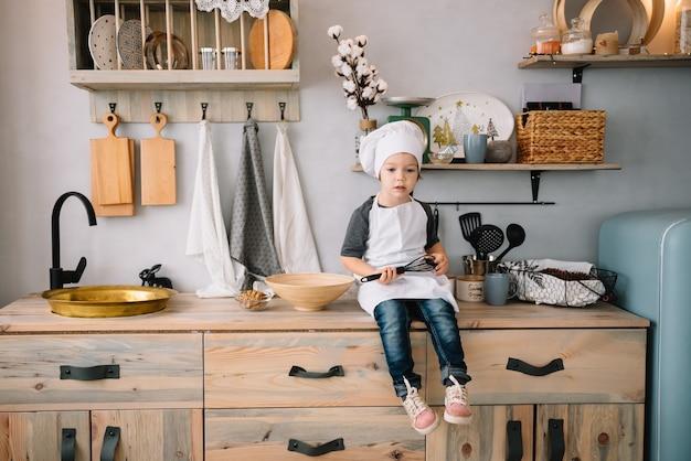 Joven en la cocina con uniforme de chef cocinando