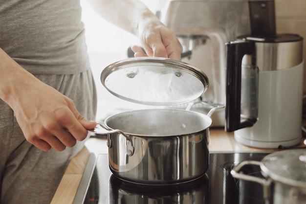 Joven cocinando alimentos frescos en casa y abriendo la tapa de la olla humeante.