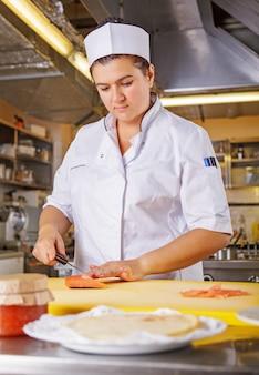 Joven cocinera cocinera vestida con uniforme blanco corta pescado salmón sobre la mesa en la cocina del restaurante