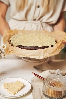 Joven cocinera haciendo un delicioso pastel de chocolate con crema sobre una mesa blanca