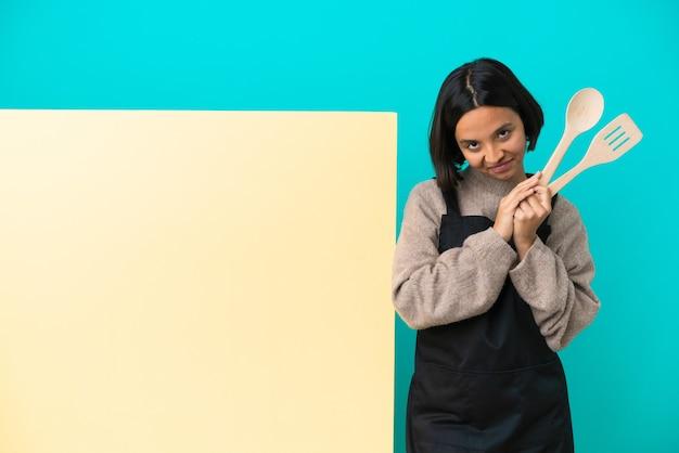 Joven cocinera de raza mixta con un gran cartel aislado sobre fondo azul mantiene la palma unida. la persona pide algo