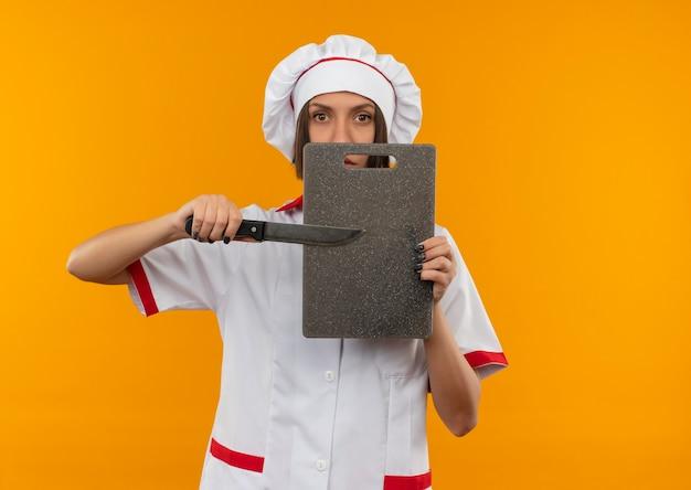 Joven cocinera en uniforme de chef apuntando con un cuchillo a la tabla de cortar y mirando a cámara aislada sobre fondo naranja con espacio de copia