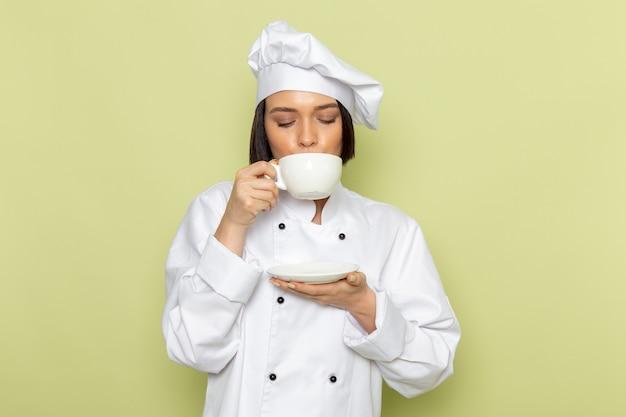 Una joven cocinera de vista frontal en traje de cocinero blanco y gorra tomando café en la pared verde