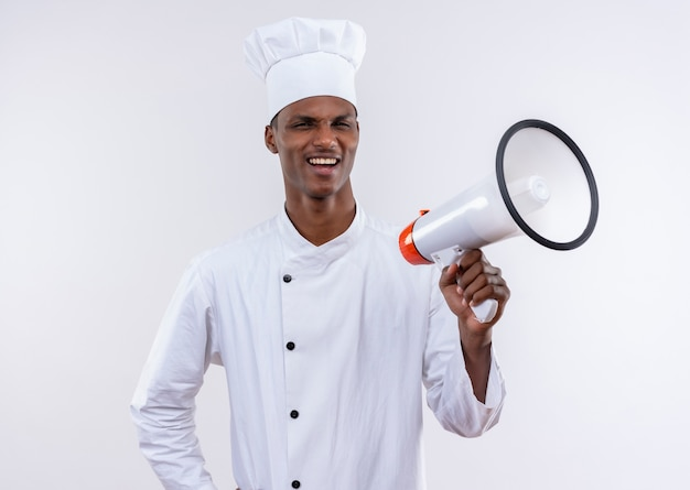 Joven cocinero afroamericano molesto en uniforme de chef tiene altavoz aislado sobre fondo blanco con espacio de copia