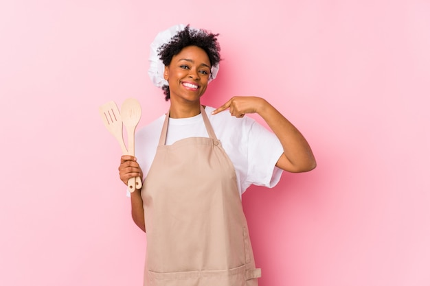 Joven cocinero afroamericano mujer persona señalando con la mano a una camisa