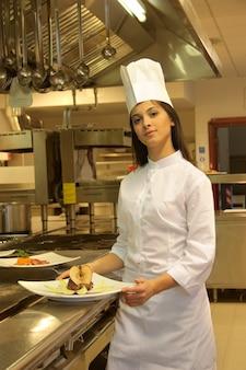 Joven cocinero en la cocina de un restaurante.