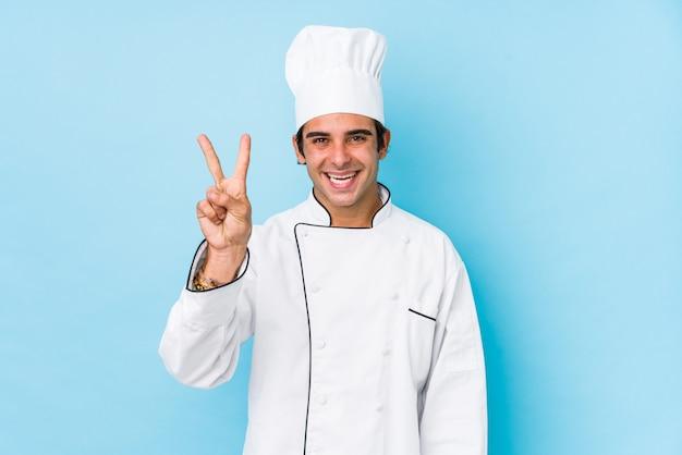 Joven cocinero hombre aislado mostrando el número dos con los dedos.