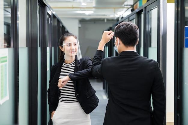 Joven colega de negocios asiático con protector facial, mascarilla y saludo de codo en el pasillo de la oficina