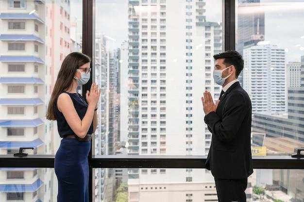 Joven colega de negocios caucásico con mascarilla con saludo de estilo tailandés por concepto de distanciamiento social en la oficina
