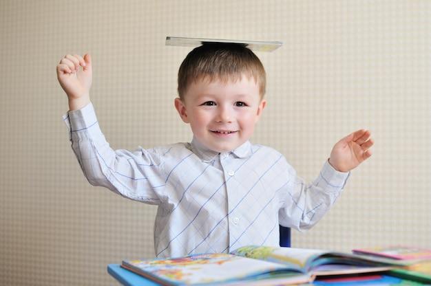 Joven colegial jugando con libros y sonriendo mientras se sienta en su escritorio en el aula