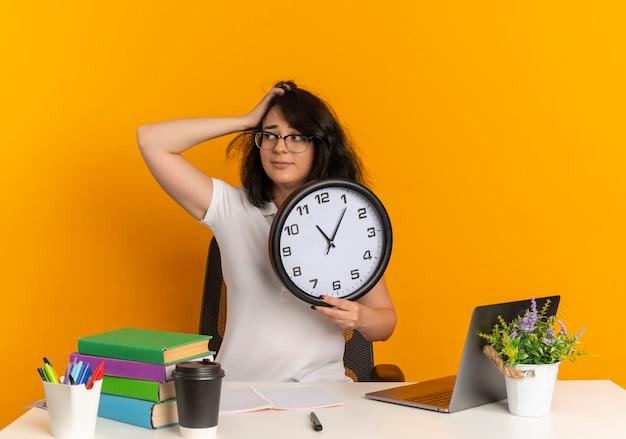 Joven colegiala bastante caucásica ansiosa con gafas se sienta en el escritorio con herramientas escolares pone la mano en la cabeza y sostiene el reloj aislado en el espacio naranja con espacio de copia