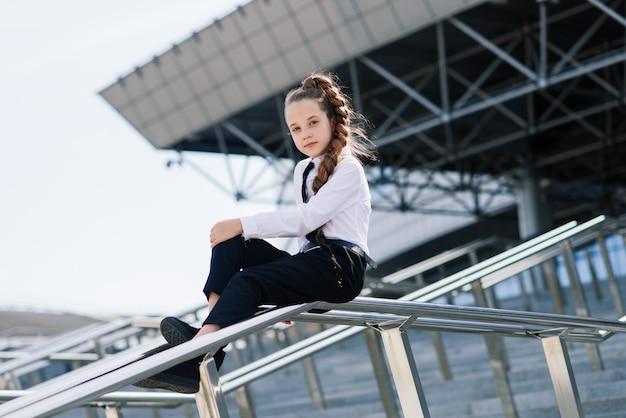 Joven colegiala en una blusa clásica blanca posando en la ciudad