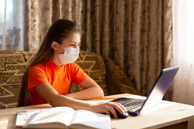 Joven colegiala en máscara médica estudiando en casa, haciendo la tarea escolar, escribiendo en el cuaderno, trabajando en la computadora portátil en línea. coronavirus en cuarentena. la educación a distancia