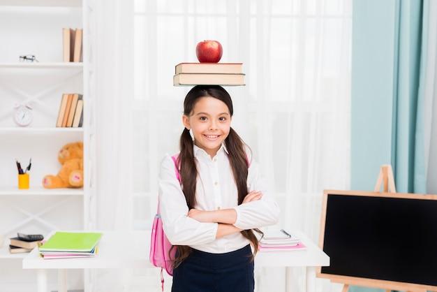 Joven colegiala en uniforme de pie brazos cruzados en aula