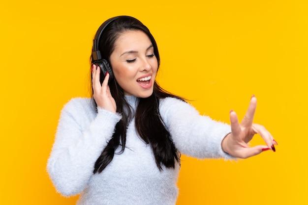 Joven colombiana sobre pared amarilla aislada escuchando música y cantando
