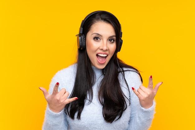 Joven colombiana sobre pared amarilla aislada escuchando música haciendo gesto de rock