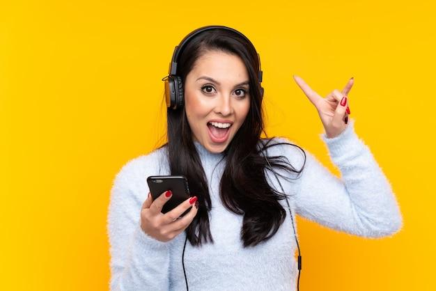 Joven colombiana sobre pared amarilla aislada escuchando música con un móvil haciendo gesto de rock