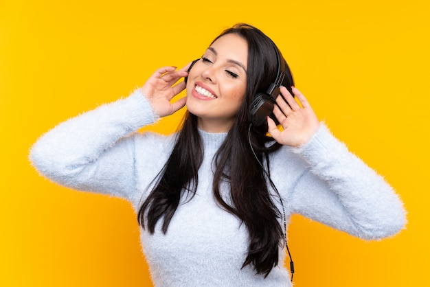 Joven colombiana sobre pared amarilla escuchando música y cantando