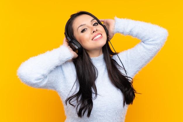 Joven colombiana sobre pared amarilla escuchando música