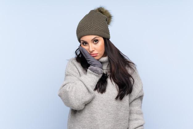 Joven colombiana con sombrero de invierno sobre pared azul aislado infeliz y frustrado
