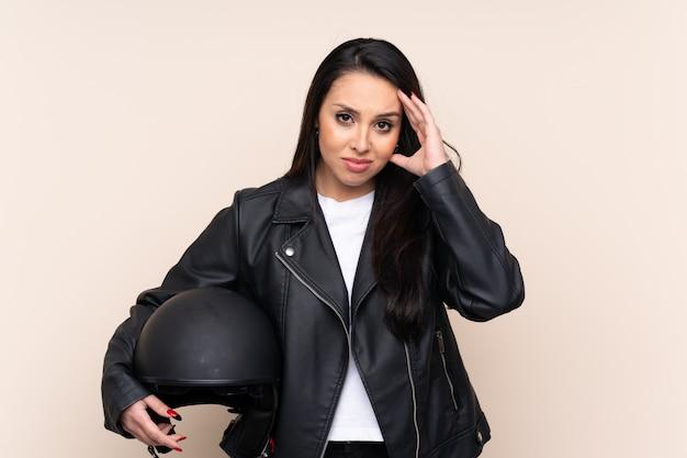 Joven colombiana sosteniendo un casco de motocicleta sobre la pared infeliz y frustrado con algo. expresión facial negativa