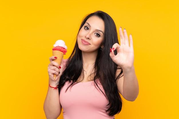Joven colombiana sosteniendo un helado de cucurucho mostrando bien firmar con los dedos