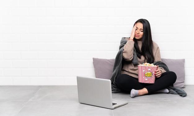 Joven colombiana sosteniendo un tazón de palomitas de maíz y mostrando una película en una computadora portátil con dolor de cabeza