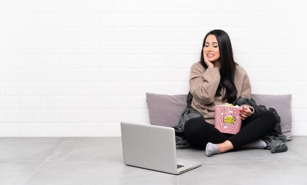 Joven colombiana sosteniendo un tazón de palomitas de maíz y mostrando una película en una computadora portátil con dolor de muelas