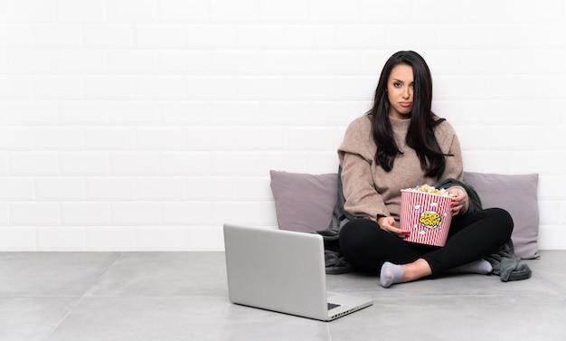 Joven colombiana sosteniendo un tazón de palomitas de maíz y mostrando una película en una computadora portátil con expresión triste y deprimida