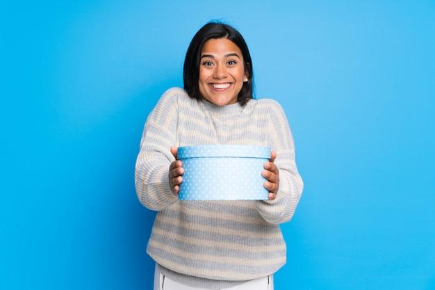 Joven colombiana con suéter sorprendida porque le han regalado