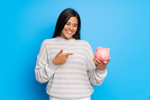 Joven colombiana con suéter sosteniendo una alcancía