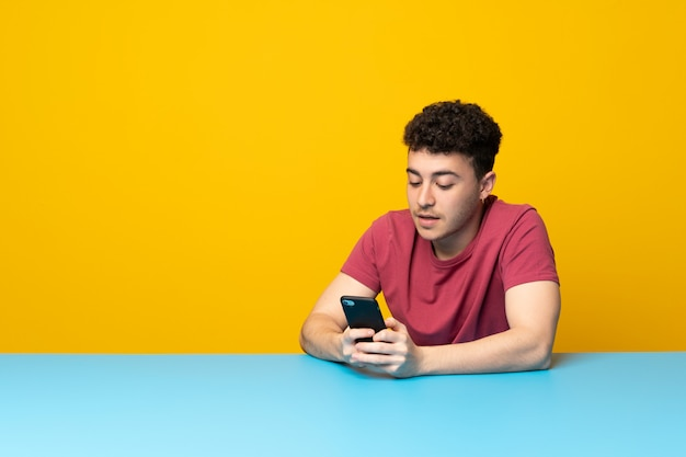 Joven con coloridas paredes y mesa enviando un mensaje con el móvil