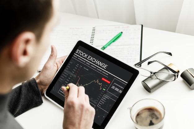 Joven comerciante está sentado en su casa a la mesa, trabajando en tableta con gráficos