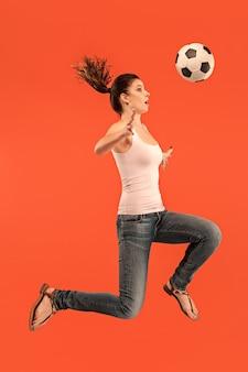 La joven como futbolista saltando y pateando la pelota en el estudio sobre un fondo rojo.