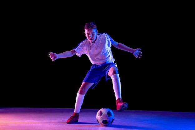Joven como jugador de fútbol o fútbol en estudio oscuro