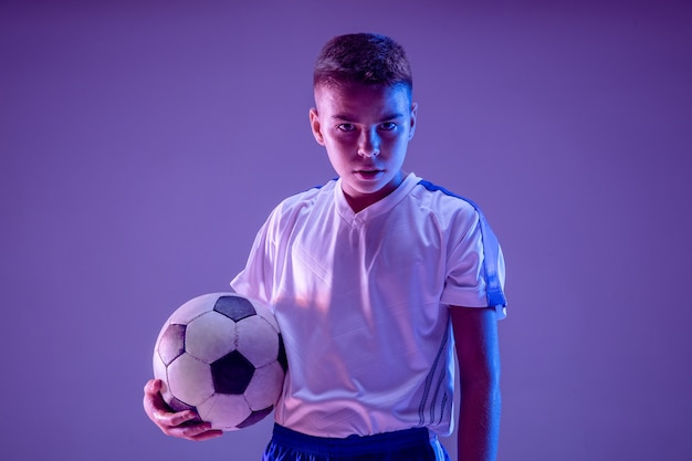 Joven como jugador de fútbol o fútbol en la pared oscura