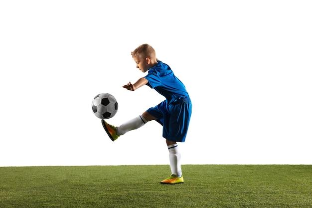 Joven como un jugador de fútbol o de fútbol en ropa deportiva haciendo una finta o una patada con el balón para un gol sobre fondo blanco de estudio. encajar jugando al niño en acción, movimiento, movimiento en el juego.