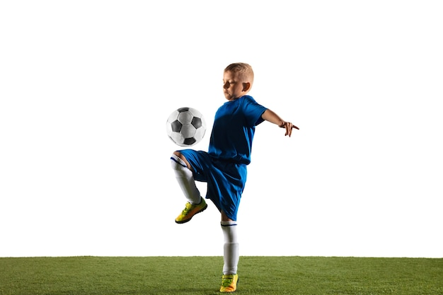 Joven como un jugador de fútbol o fútbol en ropa deportiva haciendo una finta o una patada con el balón para un gol sobre fondo blanco.