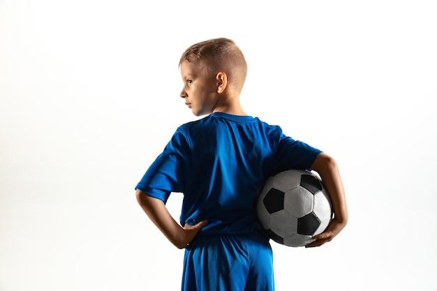 Joven como un jugador de fútbol o de fútbol en ropa deportiva de pie con el balón como un ganador, el mejor delantero o portero sobre fondo blanco. encajar jugando al niño en acción, movimiento, movimiento en el juego.
