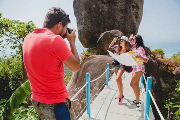 Joven compañía de amigos haciendo turismo, tomando fotografías, viajando en tailandia