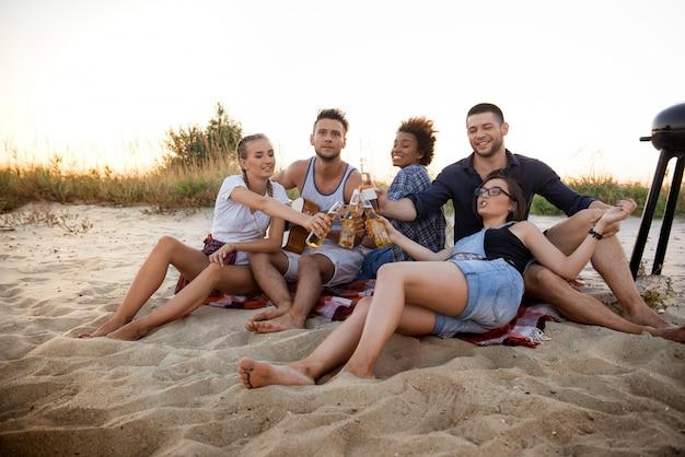 Joven compañía de amigos regocijándose, descansando en la playa durante el amanecer