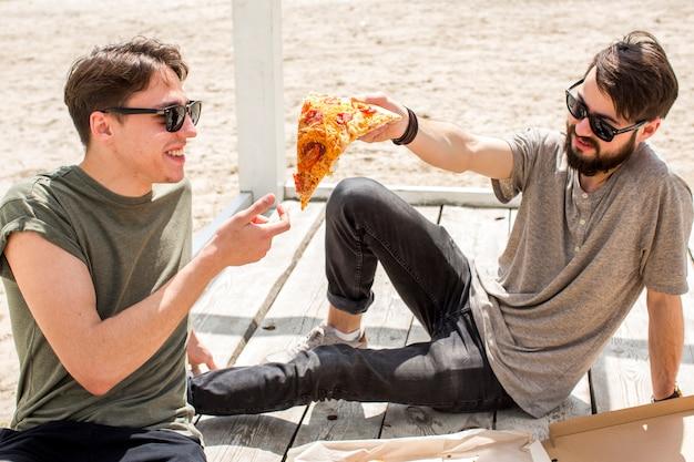 Joven compartiendo un pedazo de pizza con un amigo en la playa