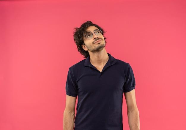 Joven complacido en camisa negra con gafas ópticas busca aislado en la pared rosa
