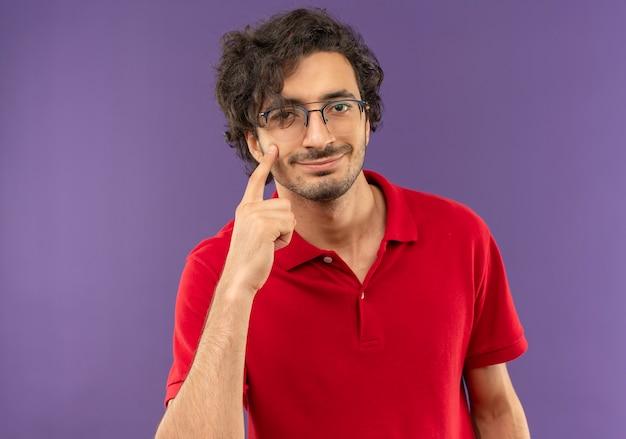 Joven complacido en camisa roja con gafas ópticas apunta al ojo aislado en la pared violeta