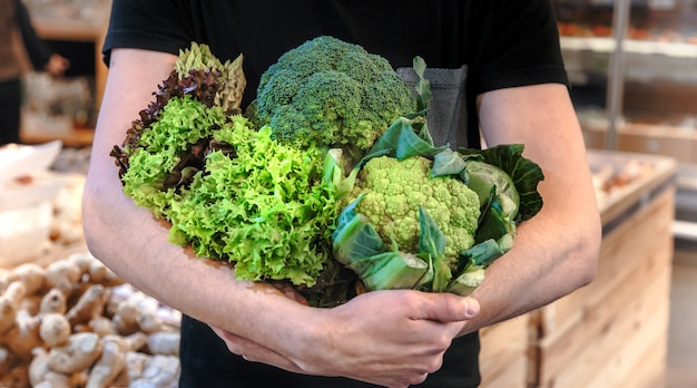 Joven comprando verduras en el mercado